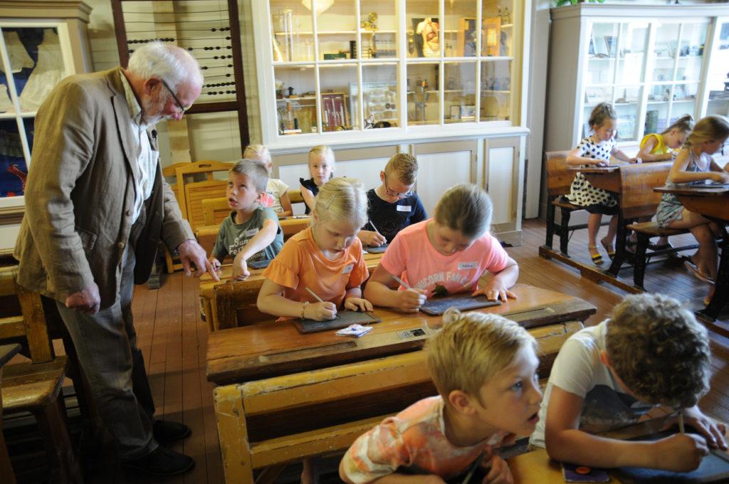 Het klaslokaal van De Meestoof is aangekleed met schoolbanken, diverse Isings-kaarten, de kroontjespen met houder